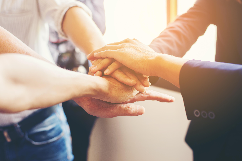 grupo-de-pessoas-com-as-mãos-umas-sobre-as-outras