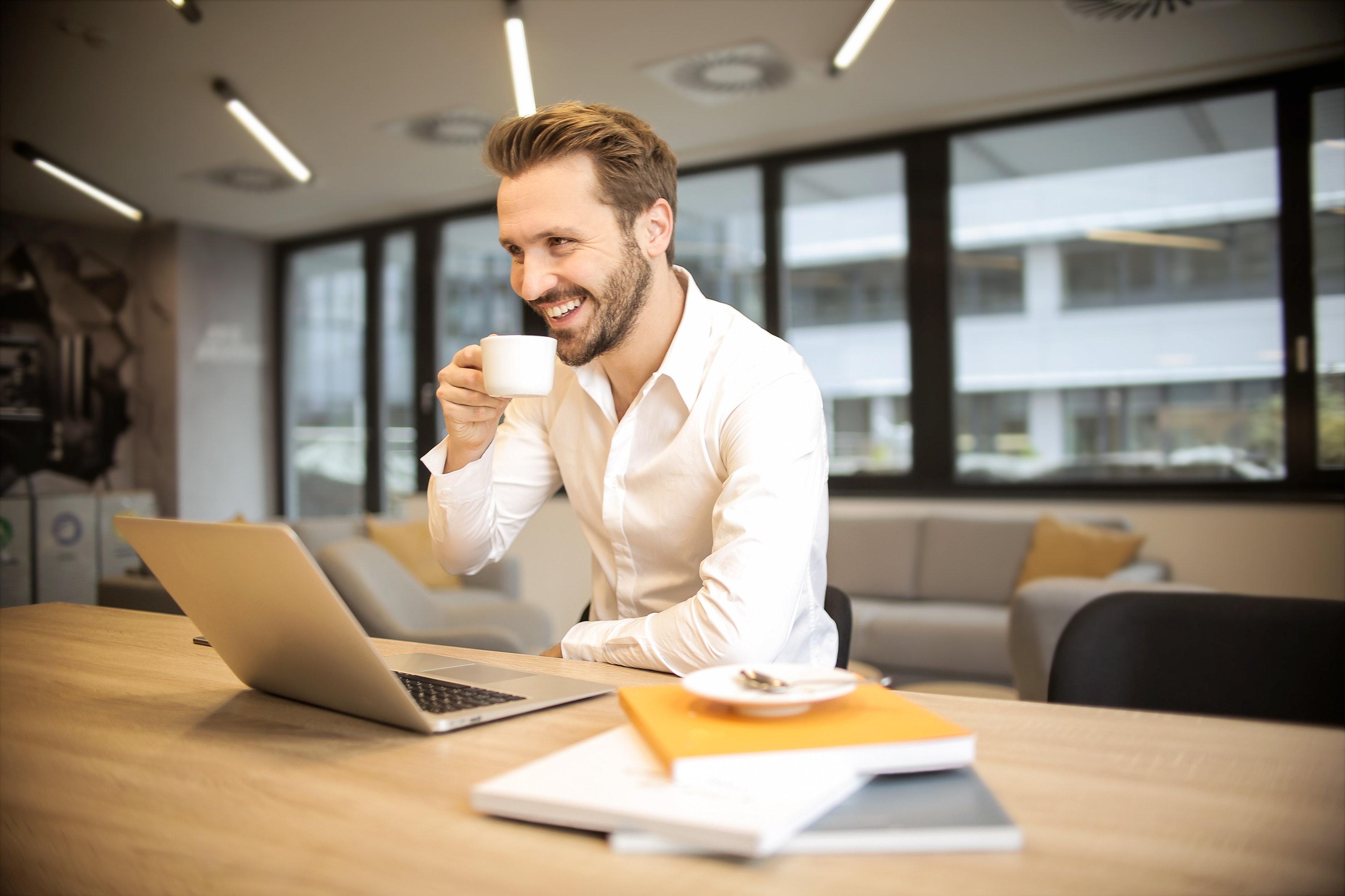 Homem tomando café e sorrindo na frente de um laptop