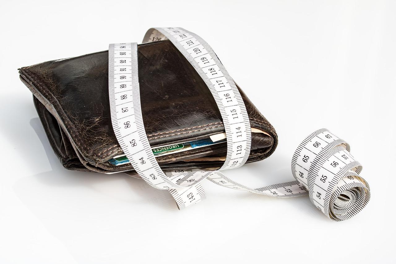 carteira com dinheiro e fita métrica em volta
