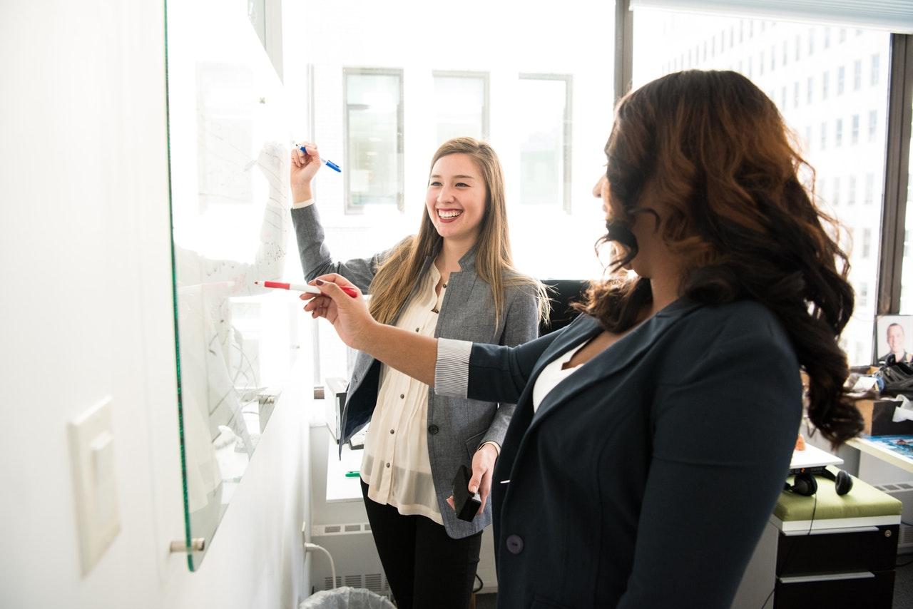 duas mulheres em frente a quadro branco