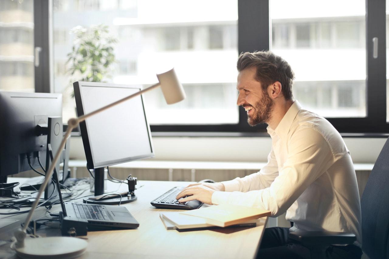 Homem sorrindo em frente ao computador